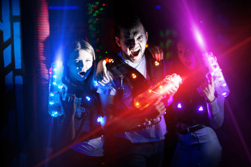 Young people with laser pistols in bright beams