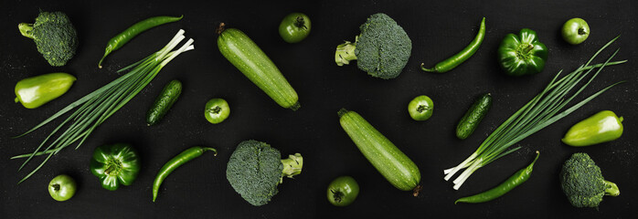 Fresh green vegetables on rustic dark stone background, top view