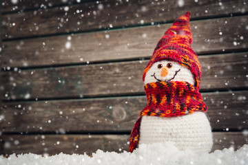 little knitted snowmans on soft snow on wooden background