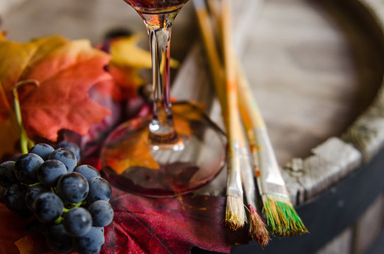 Glass of red wine, grapes and paint brushes on a wine barrel
