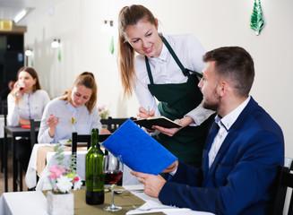 Businessman is giving order to female waiter in luxury restaurante