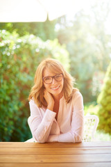 Outdoor portrait of a confident smiling woman sitting at terrace desk.