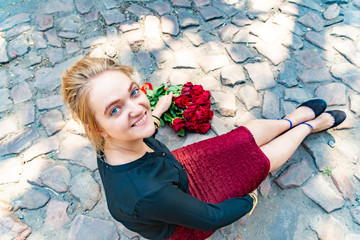 A beautiful and sexy girl sits on a brick road, and a bouquet of red roses lies side by side on the floor.