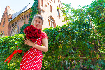 Beautiful and sexy girl holding a bouquet of red roses on the background of an old red castle.