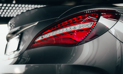 Closeup modern luxury grayBack lights headlight and head lamp of powerful beast sport car . Dealership office showroom for sale background hype epic toned wallpaper. Tuning design Automobile rental