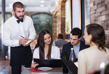 Employee waiter man taking order from guests