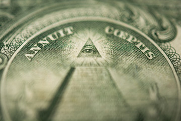 Eye of Providence or all-seeing eye sign, detail in the banknote of one dollar. Selective focus