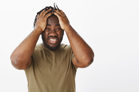 What can I do, help. Anxious devestated african american in military t-shirt, holding hands on head and clenching teeth from nervous feelings, Miserable and unaware how solve problem, stuck with issue