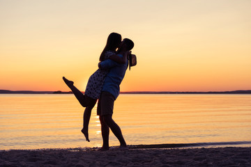 Silhouette of happy couple on beach at sunset, man taking the girl in his arms.