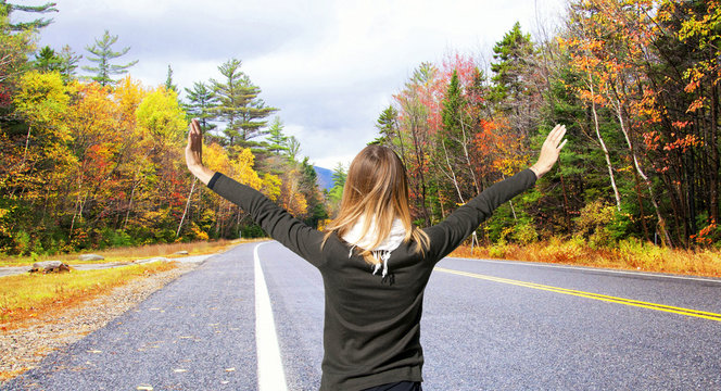 Young woman with arms raised, discovering autumn landscape in New England, USA