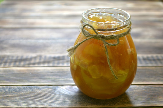 Apple jam in a jar on a wooden background