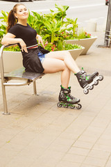 Young woman sitting wearing roller skates