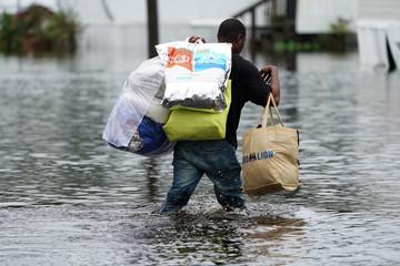 Man walks through flooded street after Hurricane Florence struck Piney Green