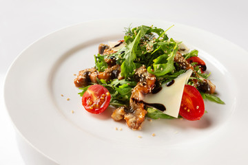 Plate with fried chicken meat served with salad, tomato, parmesan and sauce isolated at white background.