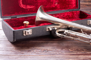Rusty trumpet and red velvet case. Vintage trumpet instrument on wooden background. Classical jazzy equipment.