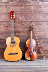 Guitar and violin on wooden background. Vintage style musical instruments on wooden surface, vertical image. Music still life.