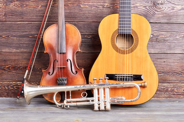 Old musical instruments on wooden background. Classical violin, trumpet and guitar. Musical equipment background.