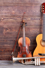 Musical instruments of vintage style. Old violin, trumpet and acoustic guitar on wooden background.
