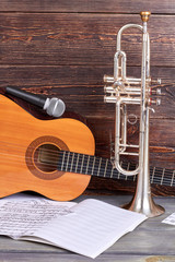 Vintage musical instruments on wooden background. Guitar with microphone, trumpet and musical notes. Professional musical equipment.