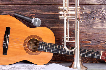 Acustic guitar, microphone and trumpet. Retro musical equipment on wooden background. Equipment for musician.