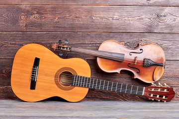 Musical instruments on wooden background. Acoustic guitar and violin. Professional classical equipment for musician.