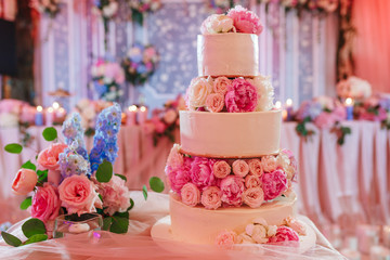 White wedding cake decorated with peony roses on pink restaurant background