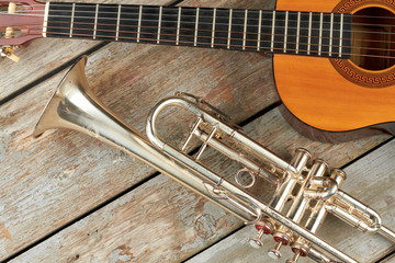 Trumpet and acoustic guitar on wooden background. Wooden guitar and classical trumpet. Retro musical instruments.
