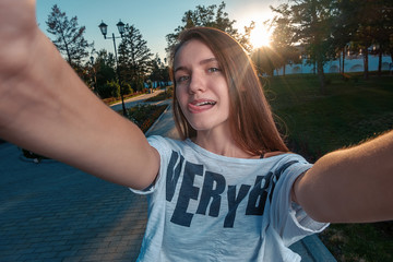 Half length of young cute caucasian reddish straight hair with tongue out woman taking a selfie, looking in camera, smiling - vanity, social network concept