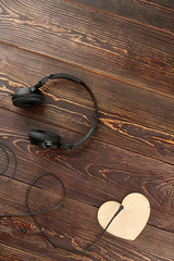Headphones and plywood heart, top view. Headphones, wooden heart and copy space, vertical image. For music lovers.