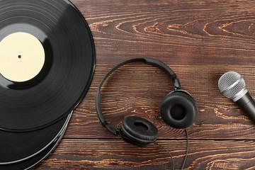 Headphones, vinyl records and microphone. Vinyl plates, headphones and microphone. Old and modern audio equipment.