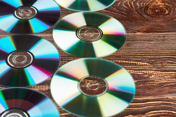 Group of colorful compact discs and copy space. Many shiny cd and dvd discs on wooden background close up. Digital media dvd disks.