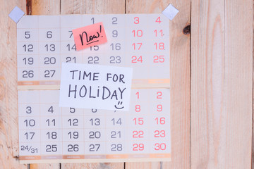 Time For Holiday written on paper note on a wall calendar with wooden background and copy space
