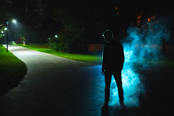 The man standing near a smoke in the park. evening night time
