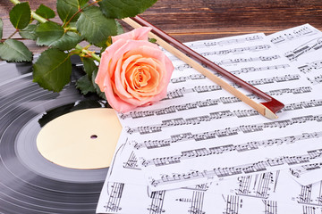 Musical sheets, vinyl record and rose. Musical instruments and rose on wooden background. Music still life.