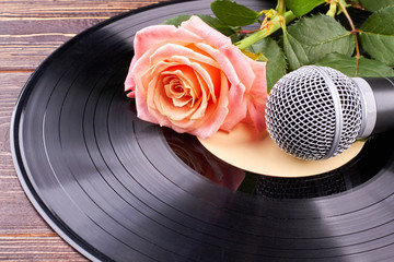 Vinyl record with microphone and rose. Musical background with black vinyl disc, pink rose and grey microphone.