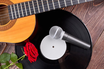 Guitar vinyl record, microphone and rose. Vinyl plate, microphone, acoustic guitar and flower. Romantic music background.