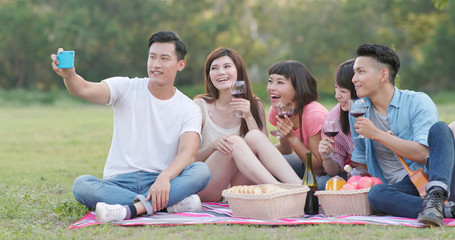 Asian Young friends taking selfie on cellphone in the park