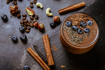 Chocolate smoothie with bluberry, nuts and chia seeds on a gey background