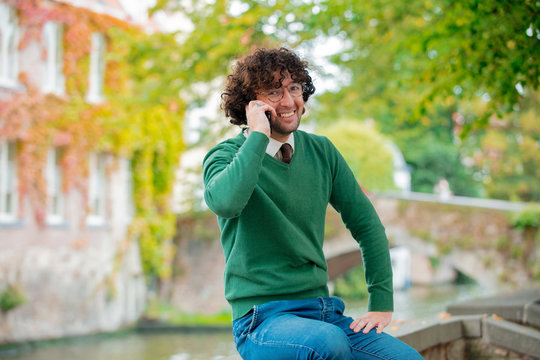 Young man with mobile phone sitting on a bridge in Bruges, Belgium