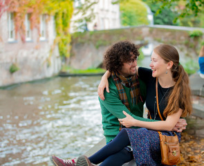 Canvas Prints Bridges Young girl and man sitting together near channel in Bruges, Belgium. Autumn season