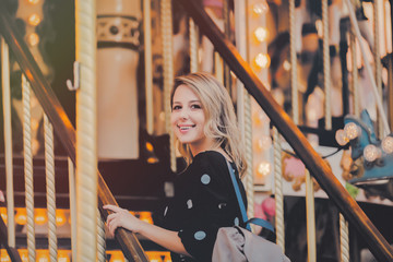 Young style girl in sunglasses and black dress stay in merry go round carousel in Strasbourg, France