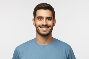 Close up portrait of young smiling handsome guy in blue t-shirt isolated on gray background Wall mural