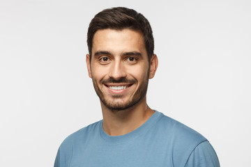 Headshot of young handsome european caucasian man isolated on gray background. wearing casual blue t-shirt, smiling happily and friendly at camera, looking confident and relaxed