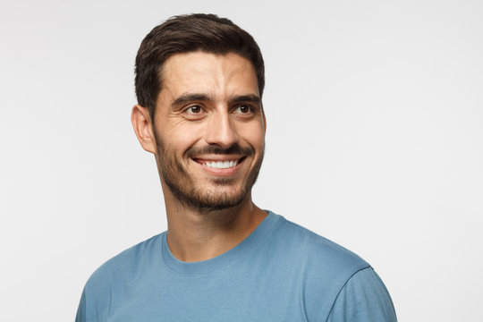 Close up portrait of smiling handsome male in blue t-shirt looking right, isolated on gray background