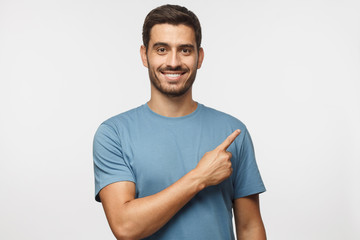 Young man in blue t-shirt pointing right with his finger isolated on gray background Wall mural