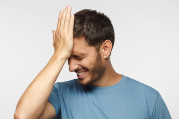 Face palm concept. Stressed out young guy making facepalm gesture with hand.