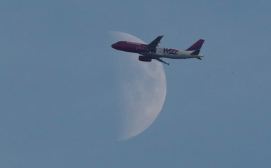 A Wizz Air passenger airplane flies past a Waxing Crescent moon, Harpenden