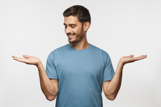 Choice concept. Portrait of young man choosing between 2 different options, holding two hands with empty space, isolated on gray background