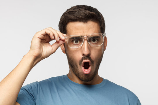 Angry young male in blue t-shirt shouting, crabbed with shock content, holding eyeglasses with one hand