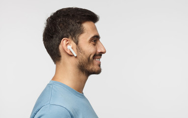 Sideways portrait of smiling young man listening to music or radio, uses modern wireless earphones, wearing blue t-shirt. Copy space for text